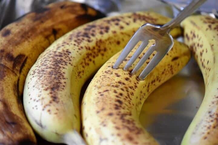 A fork piercing the outer skin of a ripe banana.