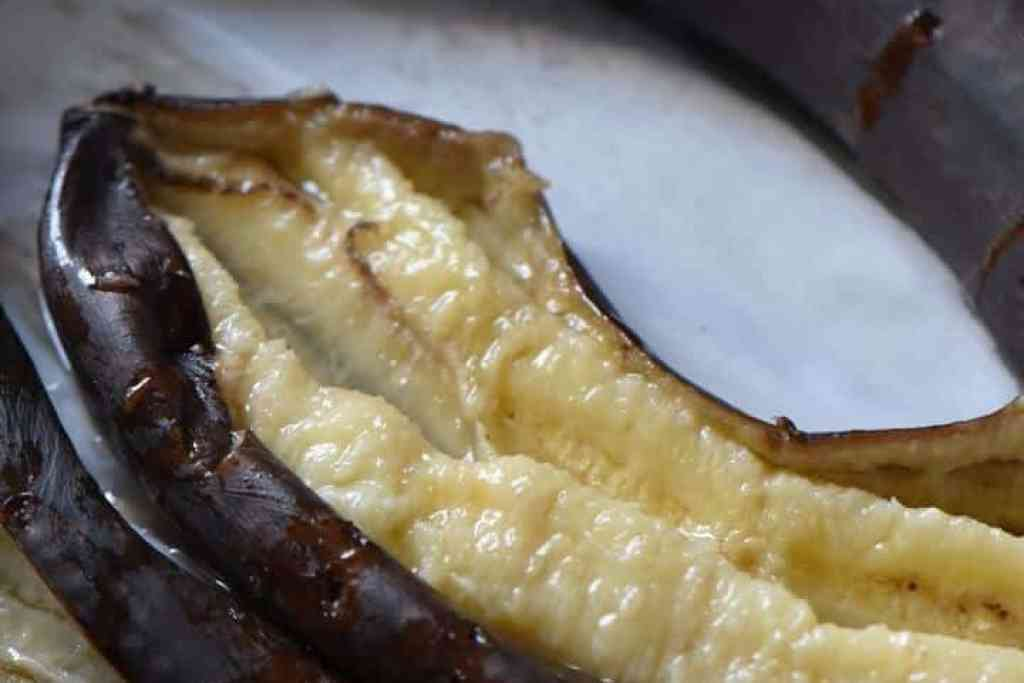 The soft interior of a baked banana is exposed.