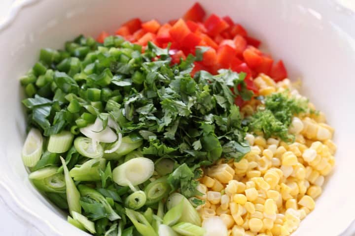 A close up shot of the chopped coriander,along side the corn and the scallions.