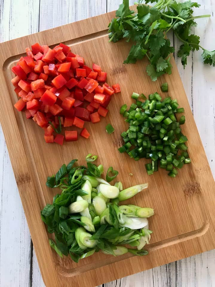 Some of the ingredients used to make the corn salad are: red pepper, jalapeno, scallions and coriander.