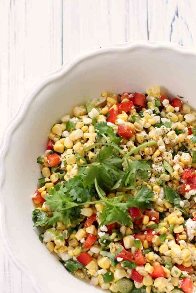 An overhead shot of a large bowl of sweet corn salad.