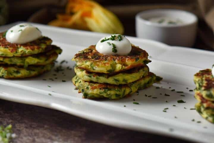 Vegetable fritters are stacked in groups of threes and are topped with a dollop of yogurt and sprinkled with chives.