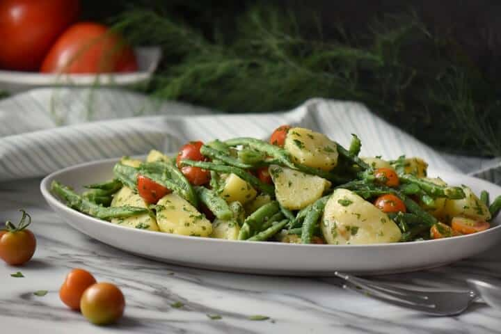 Italian potato salad with green beans and potatoes in a white serving platter.