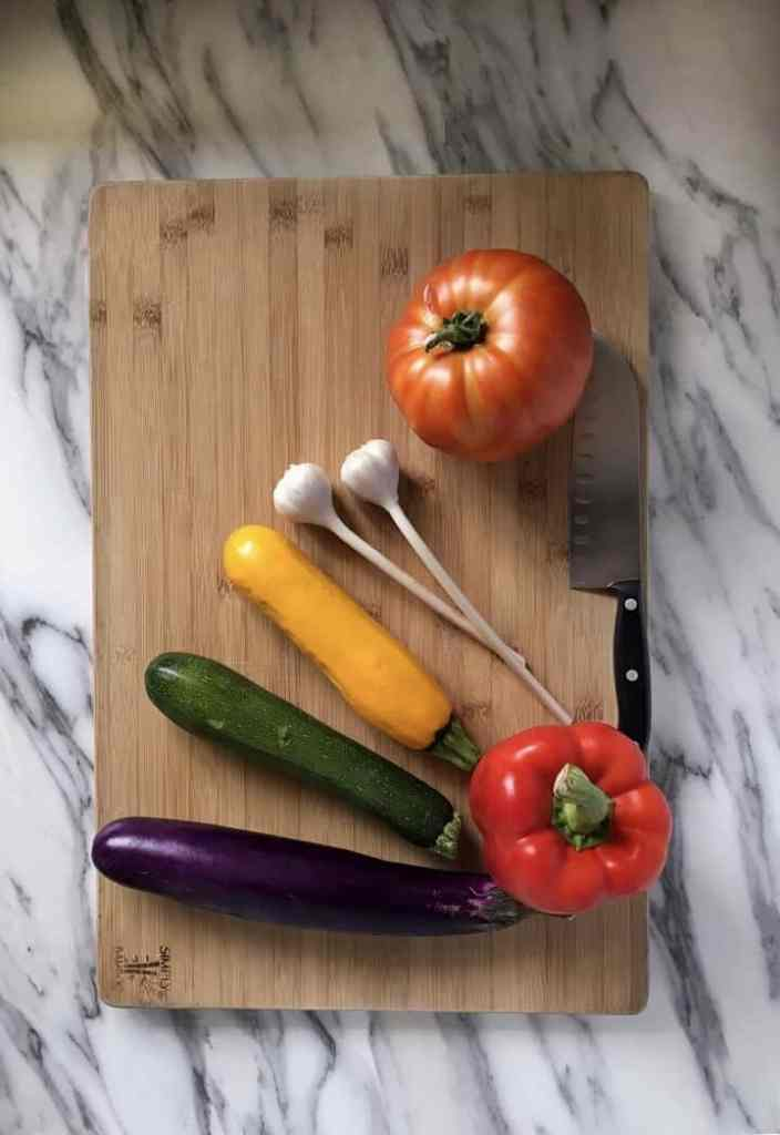Eggplant, yellow and green zucchini, garlic, tomato and red peppers are on a wooden cutting board, ready to be chopped.