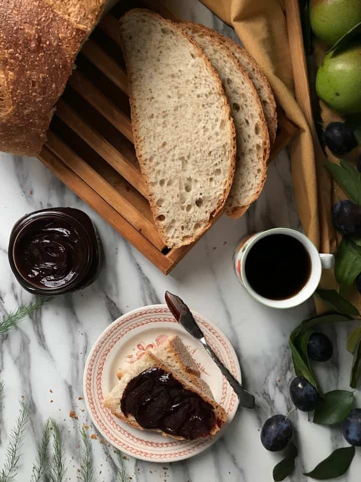 An overhead shot of a loaf of bread,a cup of coffee and plum butter spread thickly on a slice of bread.