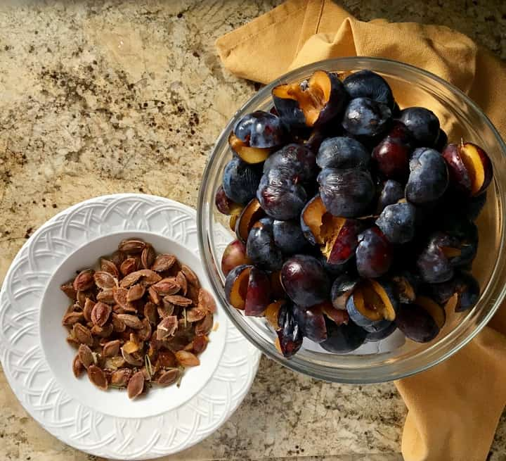 In one bowl, the pits of the prunes, in another bowl, the prune halves without the pits.