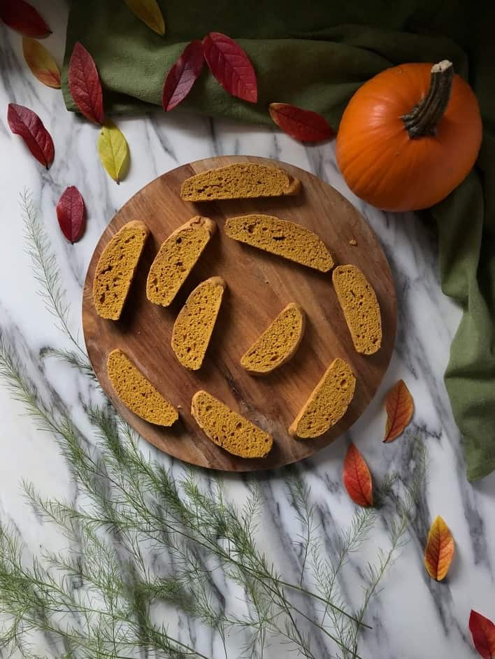 An overhead picture of pumpkin biscotti placed next to a pumpkin and autumn leaves