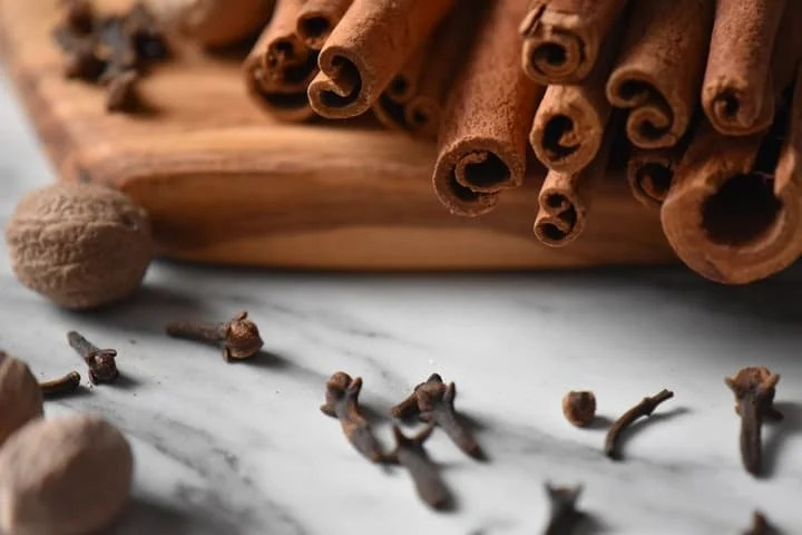 A close up of cloves, whole nutmeg and cinnamon sticks; 3 ingredients to make this allspice recipe.