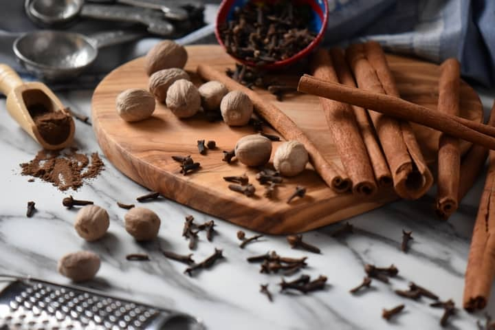 Whole nutmeg, cinnamon sticks and cloves are scattered on a wooden board. Also seen is the result of this allspice recipe, that is to say ground allspice.