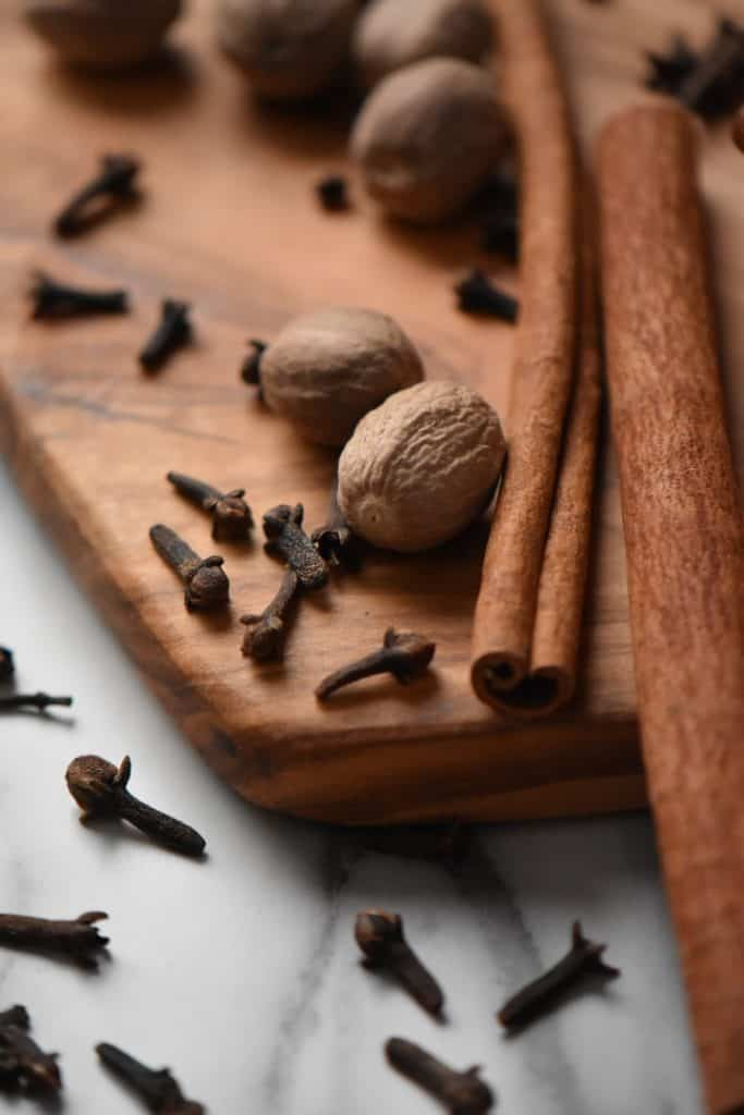 A close up of whole nutmeg, long sticks of cinnamon and cloves on a wooden board.