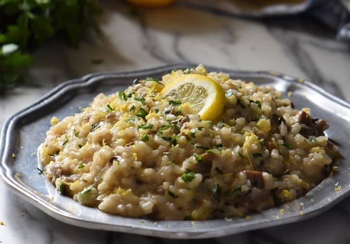 Creamy Mushroom Risotto in a pewter plate topped with lemon zest and a slice of lemon.