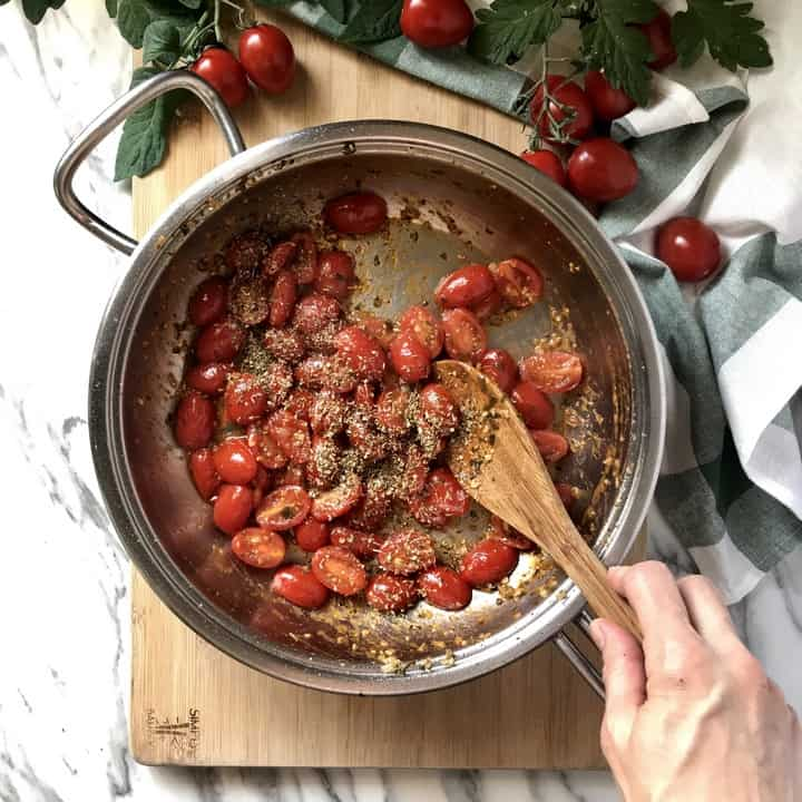Oregano is combined with a mixture of cherry tomatoes in a large pan.