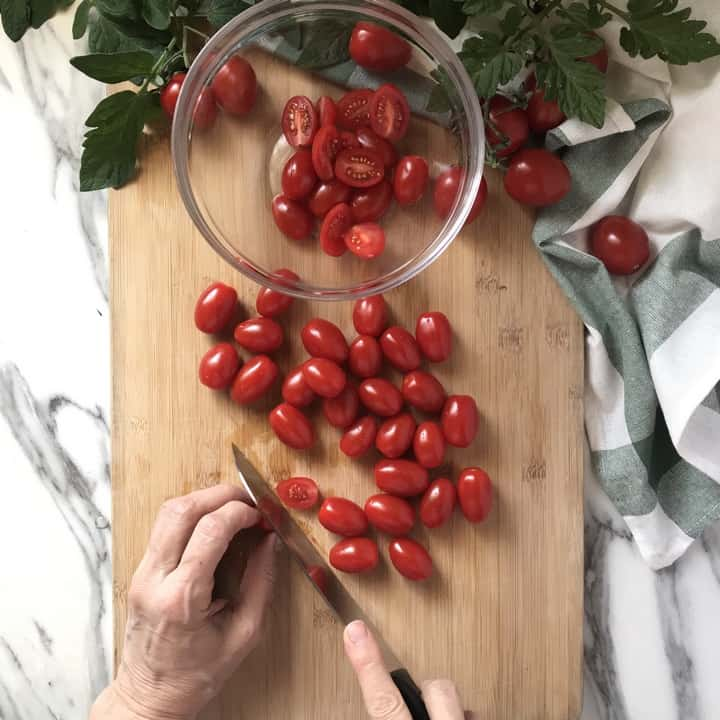 Cherry tomatoes being sliced in half on a wooden board.