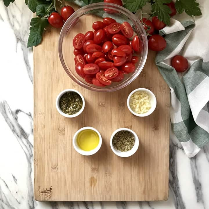 A big bowl of sliced cherry tomatoes next to smaller bowls containing pesto, olive oil, oregano and chopped garlic.