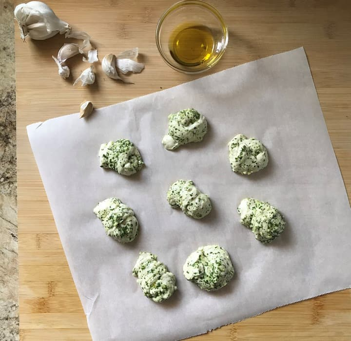 Garlic knots on a parchment paper, ready to be baked.