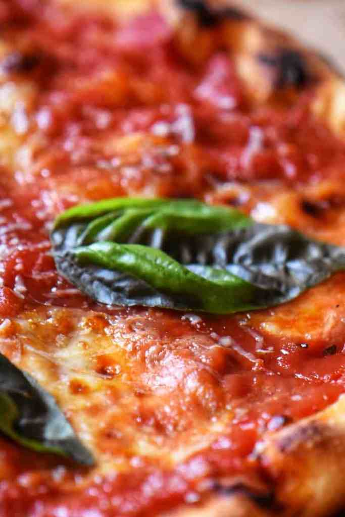 A close up of a basil leave atop a slice of margherita pizza.