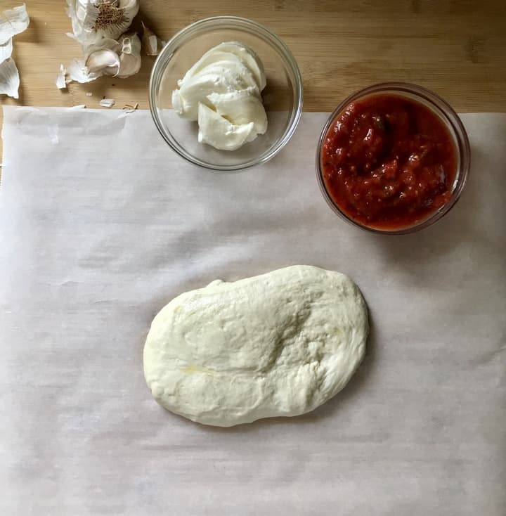 Pizza dough on parchment paper next to a bowl of pizza sauce and mozzarella.