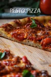 Cherry tomatoes top this pesto pizza that is on a wooden board.