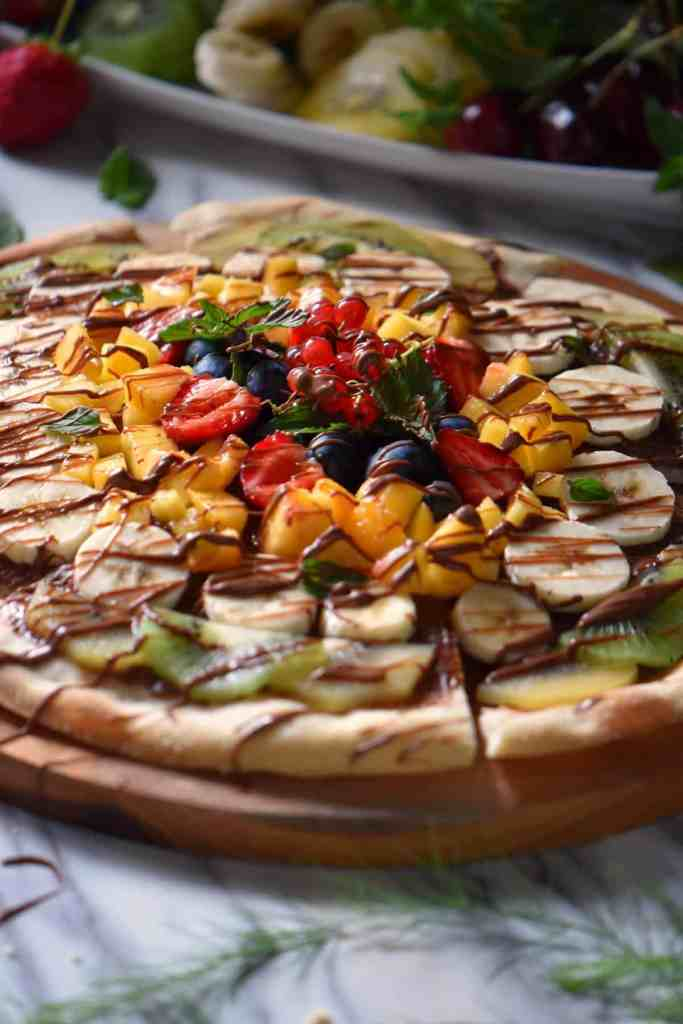 A thin pizza crust topped with seasonal fruits that have been drizzled with chocolate.
