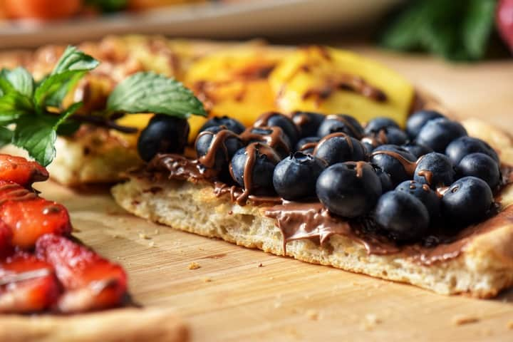 Fresh blueberries on a piece of pizza.