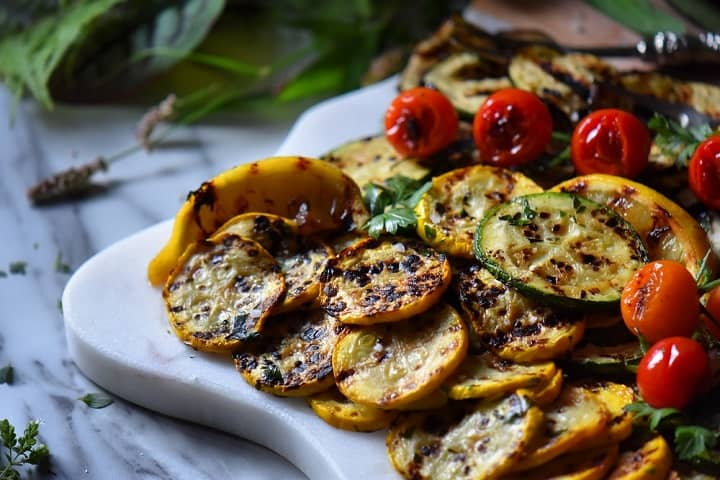 A few grilled vegetables on a white serving platter.