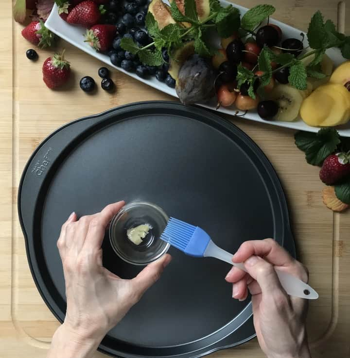 A pizza pan is about to be spread with butter with a pastry brush.