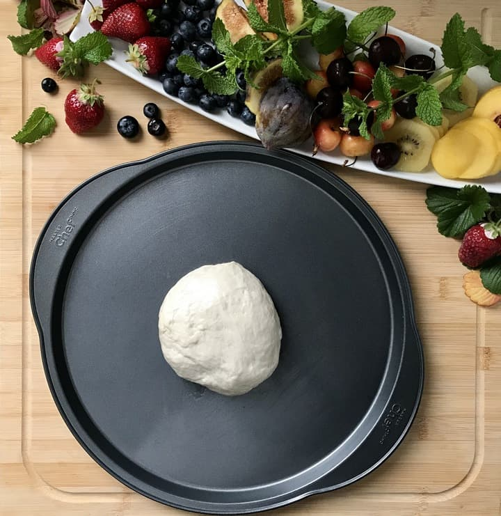 A ball of pizza dough in a greased pizza pan.