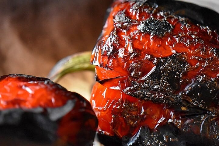 A close up of the charred skin of a roasted red pepper.