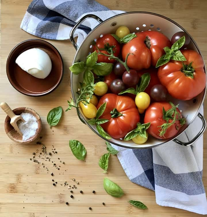 A colander filled with heirloom tomatoes, next to basil leaves, a ball of mozzarella, sea salt and pepper.