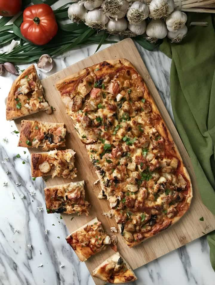 Slices of fish pizza on a wooden board, surrounded by fresh tomatoes and garlic cloves.