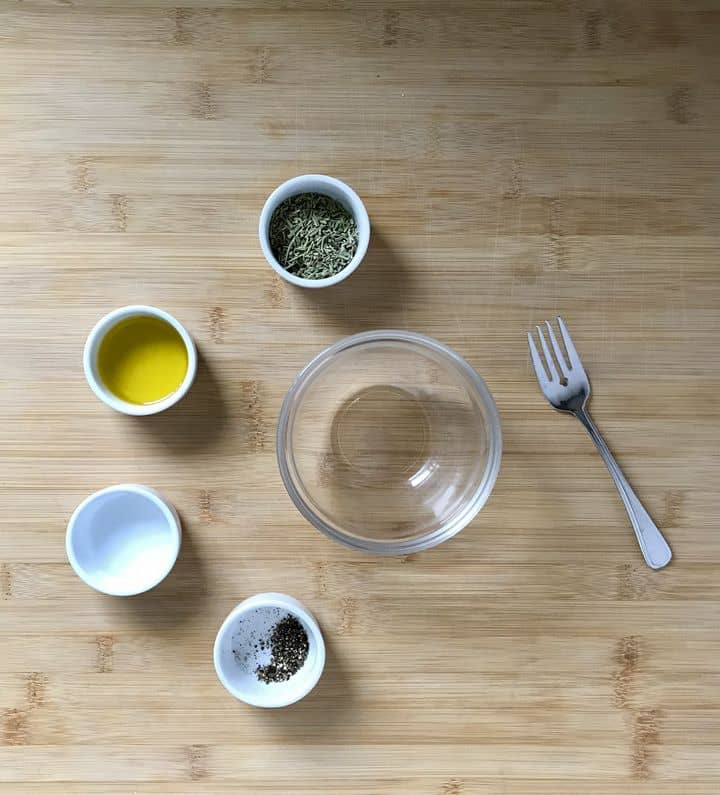 Dried rosemary, olive oil, water and pepper in small bowls.