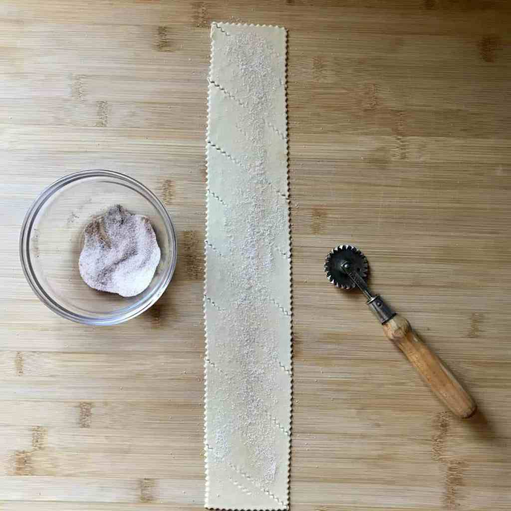 Cinnamon sugar sprinkled over pastry dough on a wooden board.