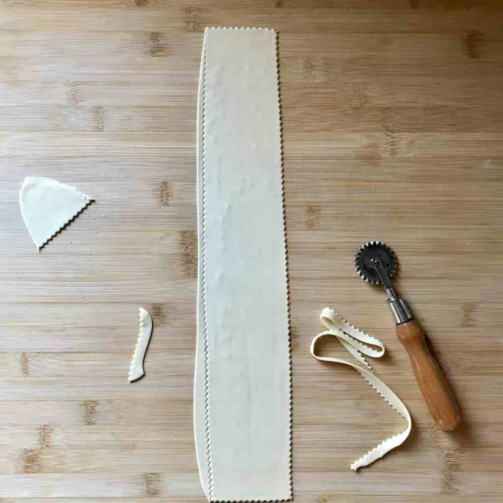 A pastry wheel is used to cut a piece of dough on a wooden board.