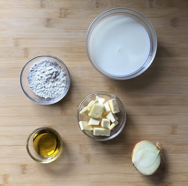 The ingredients to make the bechamel sauce on a wooden counter.