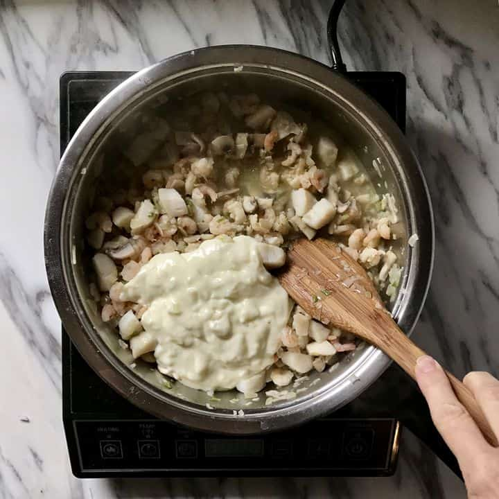 The bechamel sauce is added to the seafood mixture.