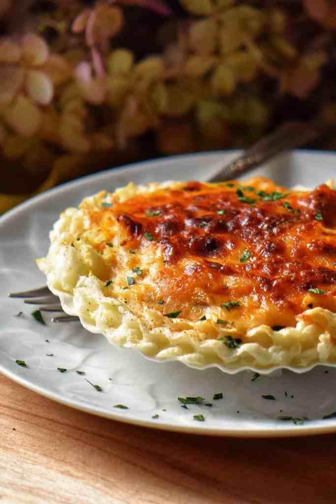 A scallop shell is filled with the French classic appetizer, Coquilles St-Jacques.