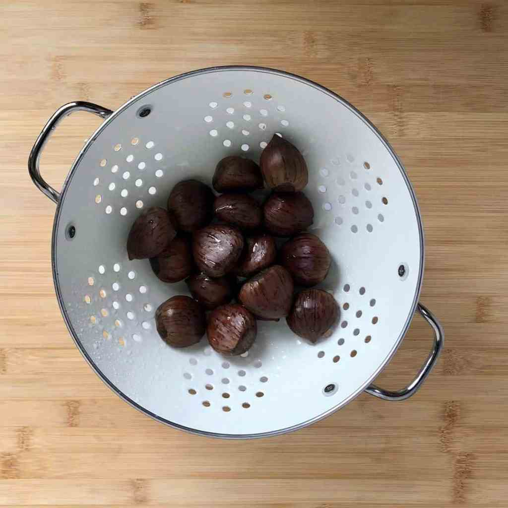 Rinsed chestnuts in a colander.