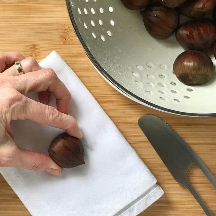 A single chestnut placed on a white tea towel, about to be scored.