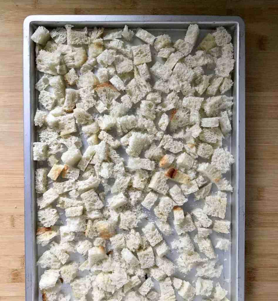 Cubed fresh bread on a rimmed baking sheet.