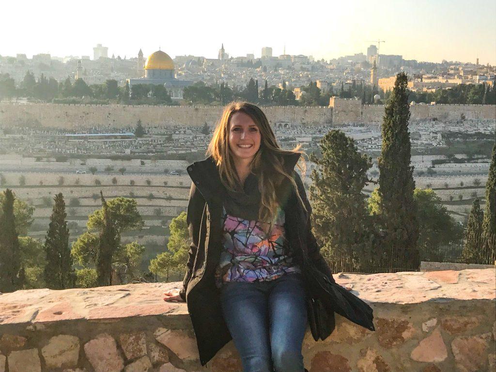 woman-sitting-on-ledge-jerusalem-behind