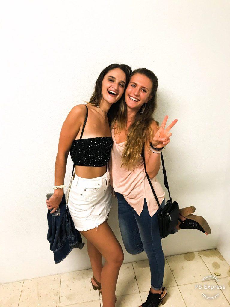 two-women-smiling-posing-white-wall