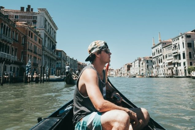 man sitting in boat alone in Venice, Italy