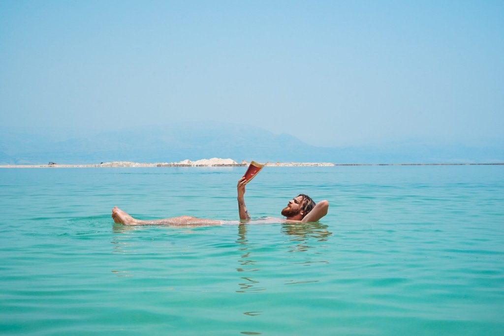 man reading floating in Dead Sea, Israel