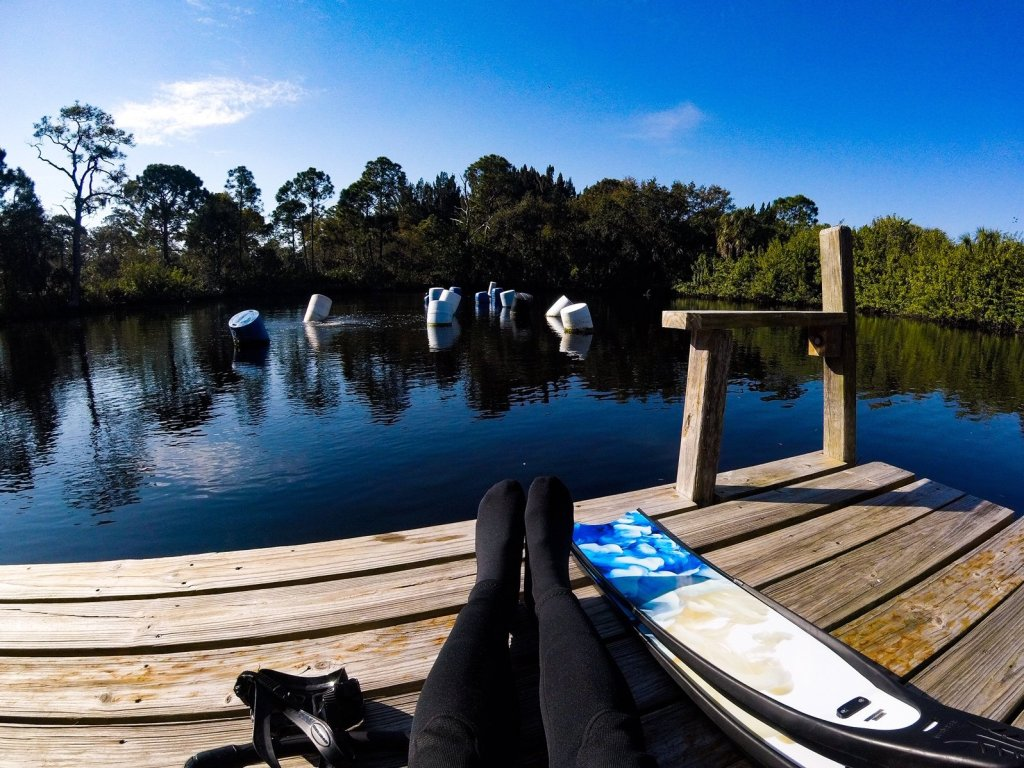 freediving fins and feet in wetsuit sitting on dock