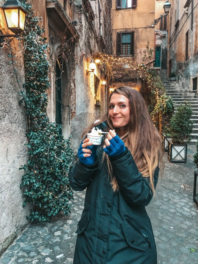 woman eating gelato in italy in winter coat