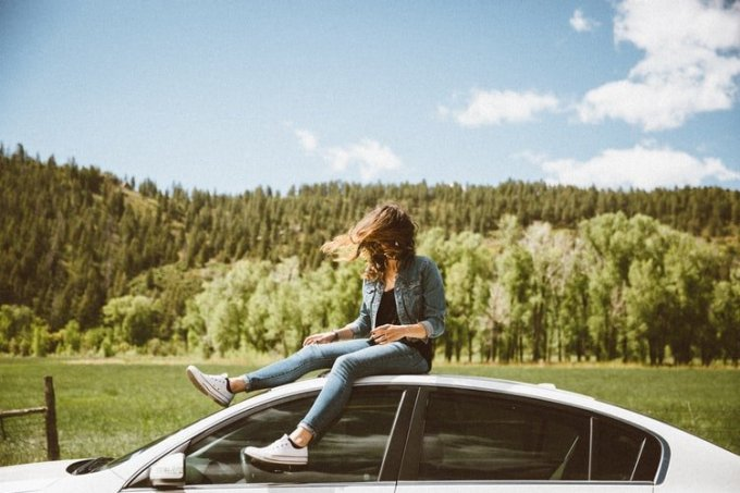 woman sitting on top of car forest background
