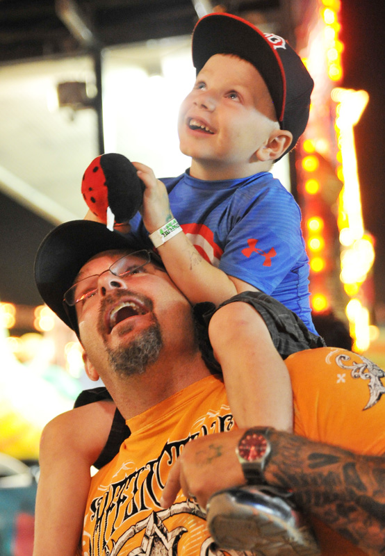 Four-year-old Dyllan Cope watches from the safety of his father Darren Cope's shoulders as his older siblings scream from a carnival ride Saturday night at the Sheridan County Fairgrounds arena.