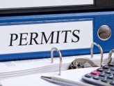 "the word ""permits"" labeled on a blue binder in a office"