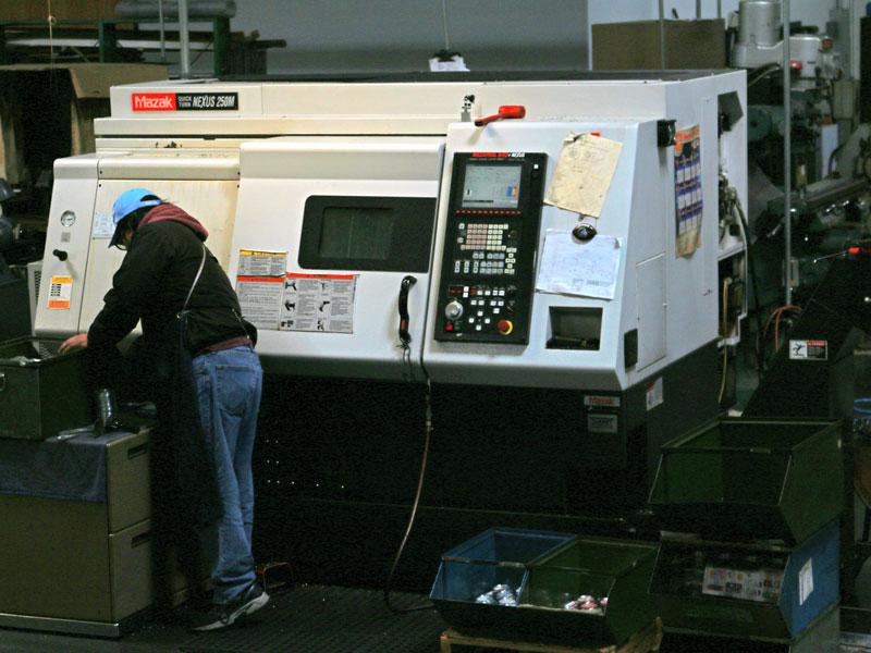 A CNC lathe operator monitors progress of a job.