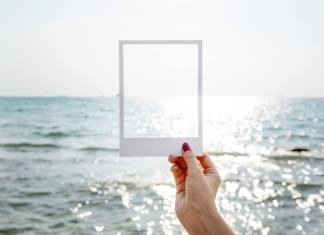 hand holding polaroid over ocean